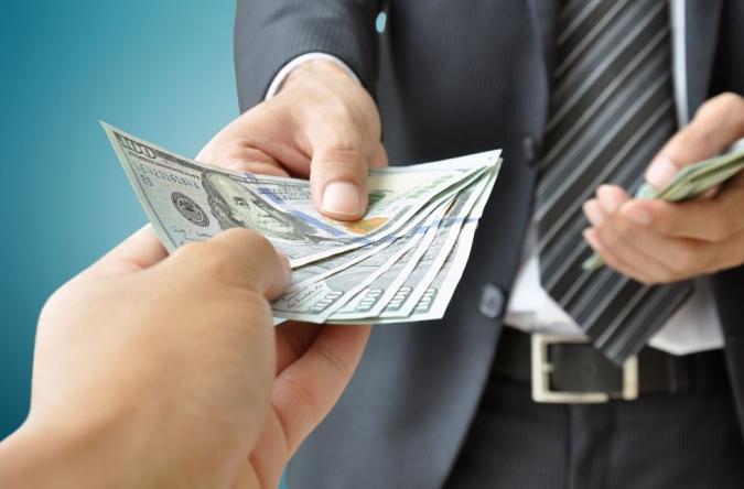 Man in suit handing over money