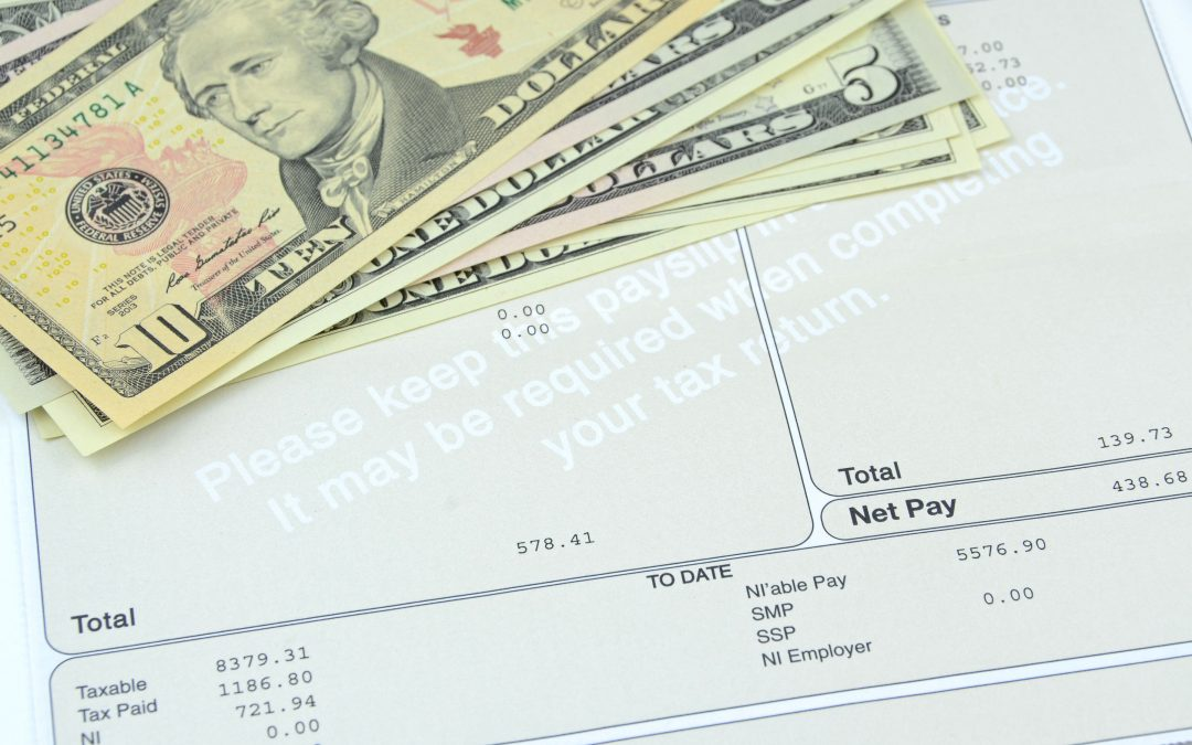 Close up of most recent pay stub and payday loan cash advance