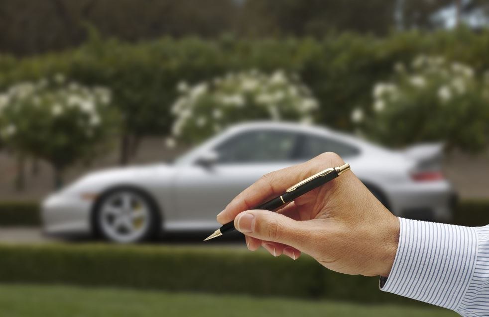 Hand holding a pen with a car in the background to indicate signing for a car title loan